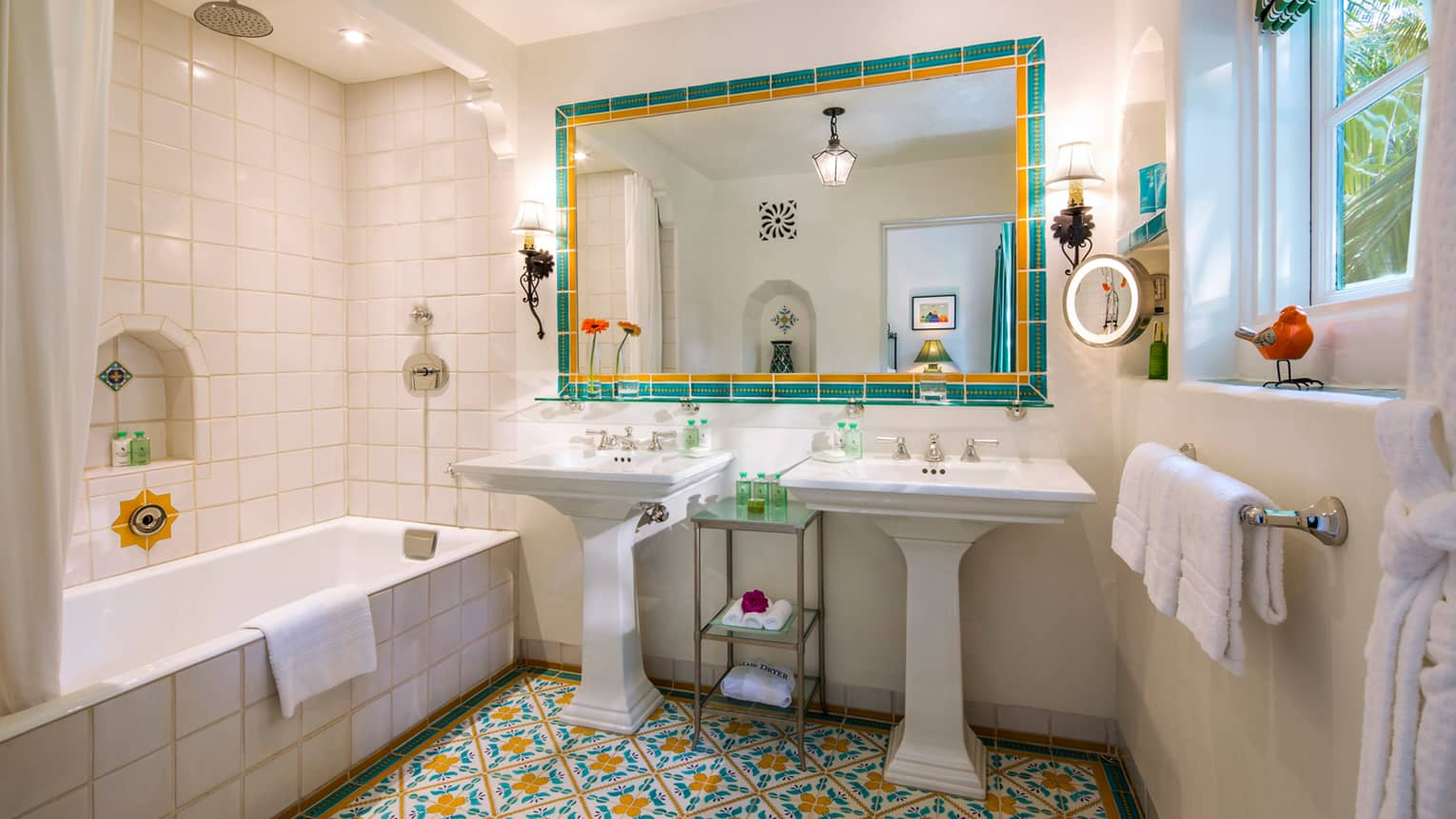 Mariposa Suite bathroom double free-standing sinks, large mirror, TV, colourful Spanish tiles