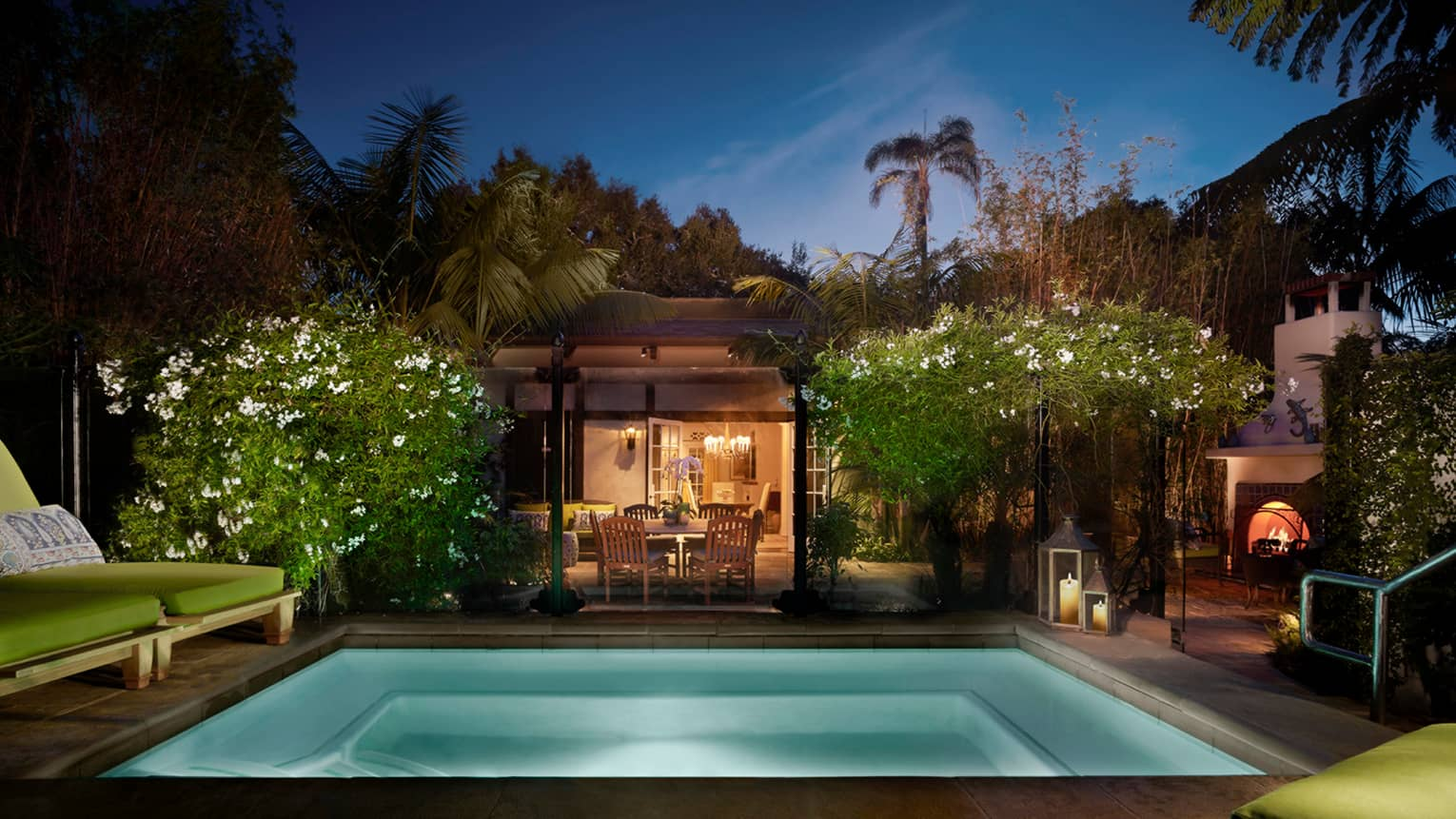Bungalow Suite backyard at night with illuminated plunge pool, tropical plants, lights from living, dining room