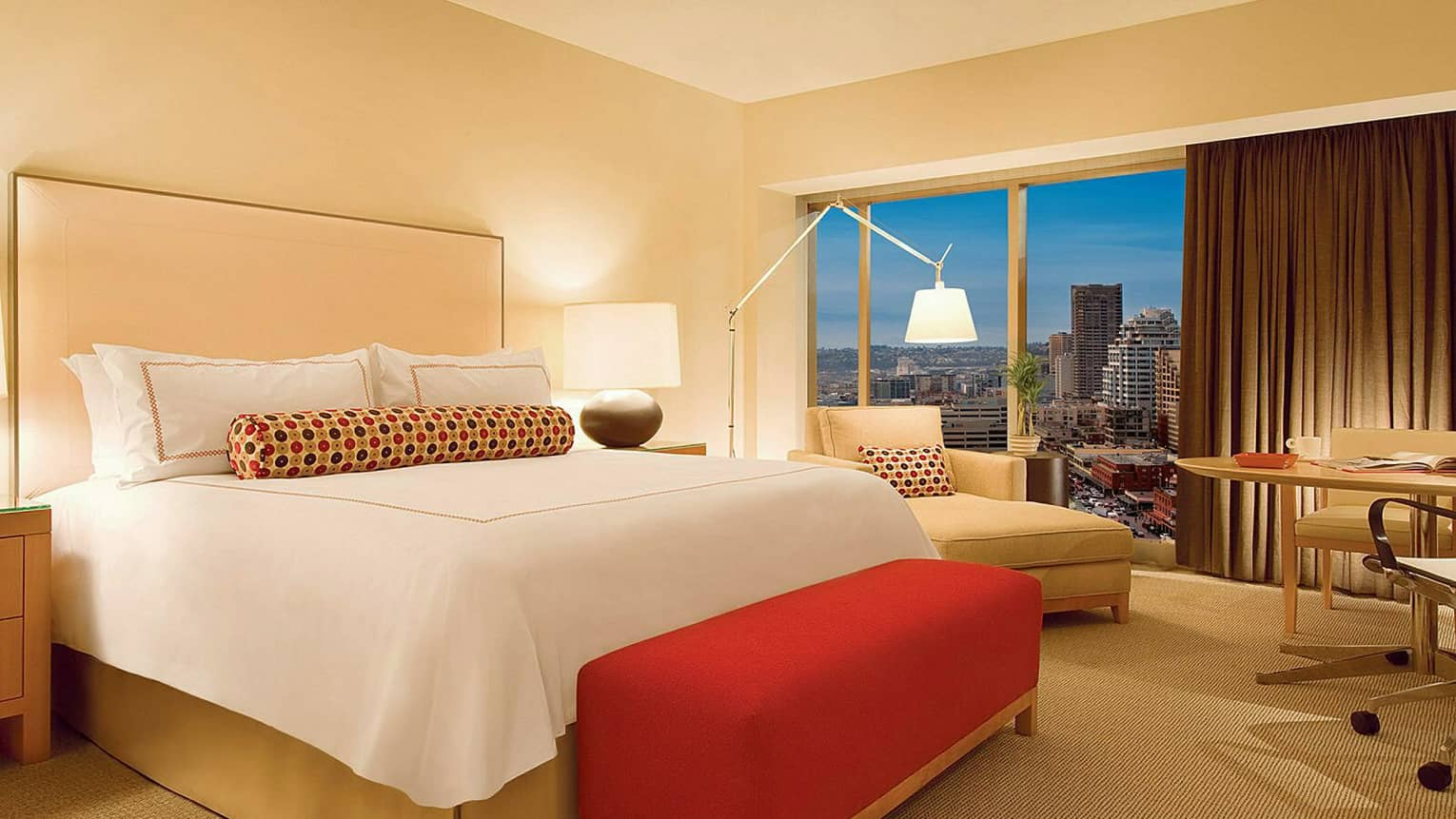 Deluxe Seattle-View Room bed with plush red bench, beige chaise in front of window, urban view