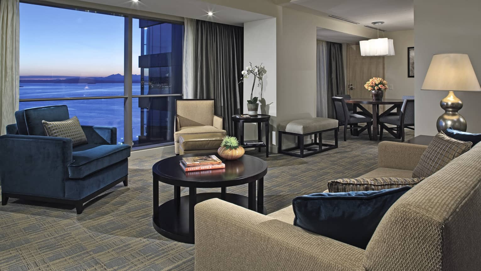 Deluxe Elliott Bay Suite large living room with dark blue armchairs, dining table, floor-to-ceiling sunset bay views