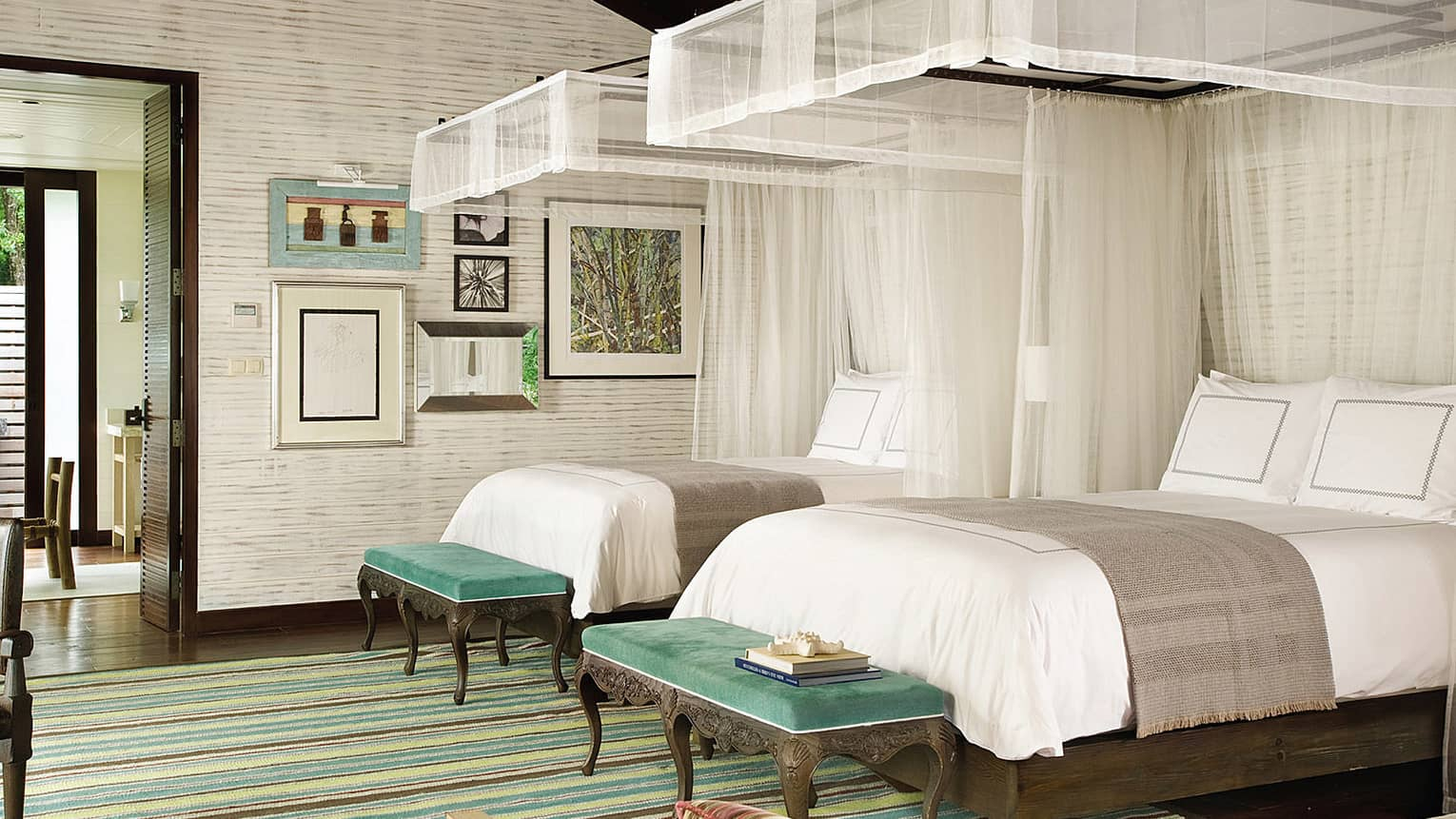 Three-Bedroom Residence Villa bedroom with double beds side-by-side, white sheer canopies, green benches