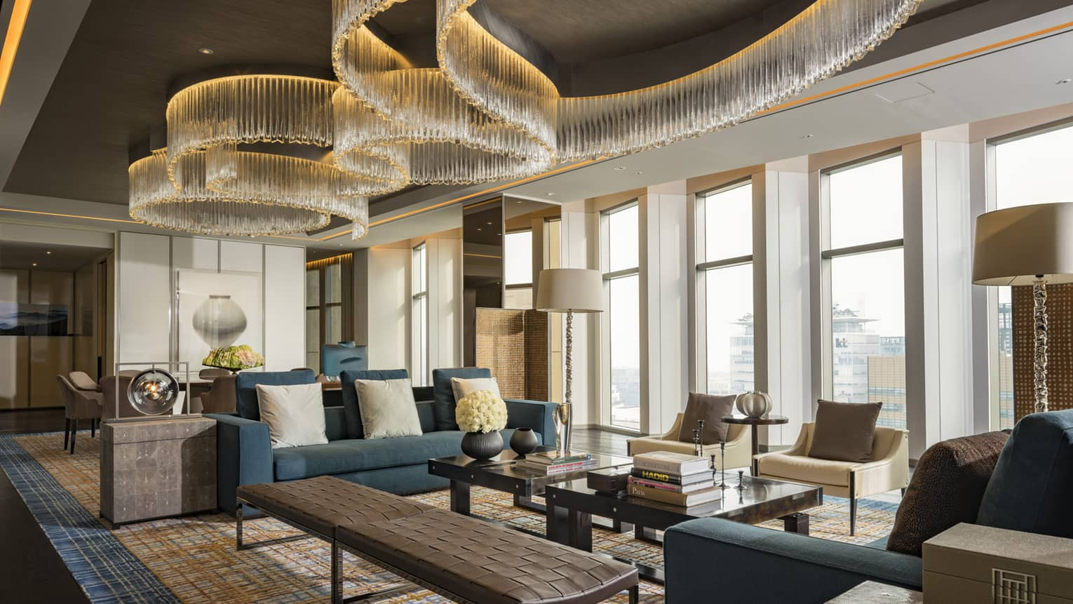 Presidential Suite seating area with large blue sofas, long leather bench, tables under modern chandeliers from soaring ceilings