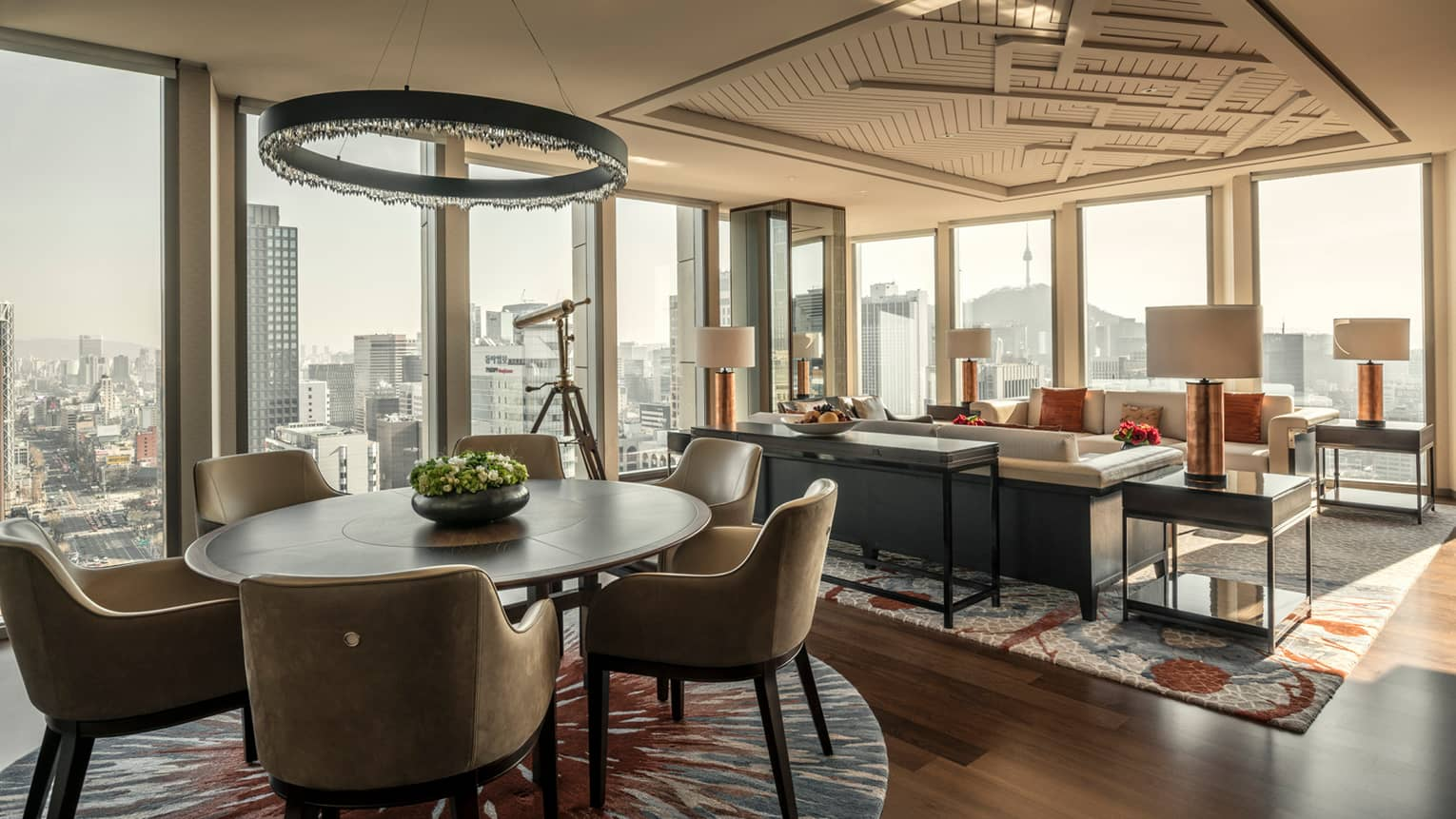 Sejong Two-Bedroom Suite round dining table under modern chandelier, seating area, corner windows