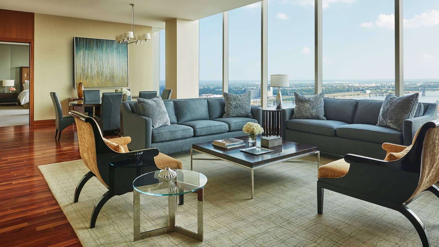 Large hotel room living area with two blue sofas, gold velvet armchairs and square coffee table