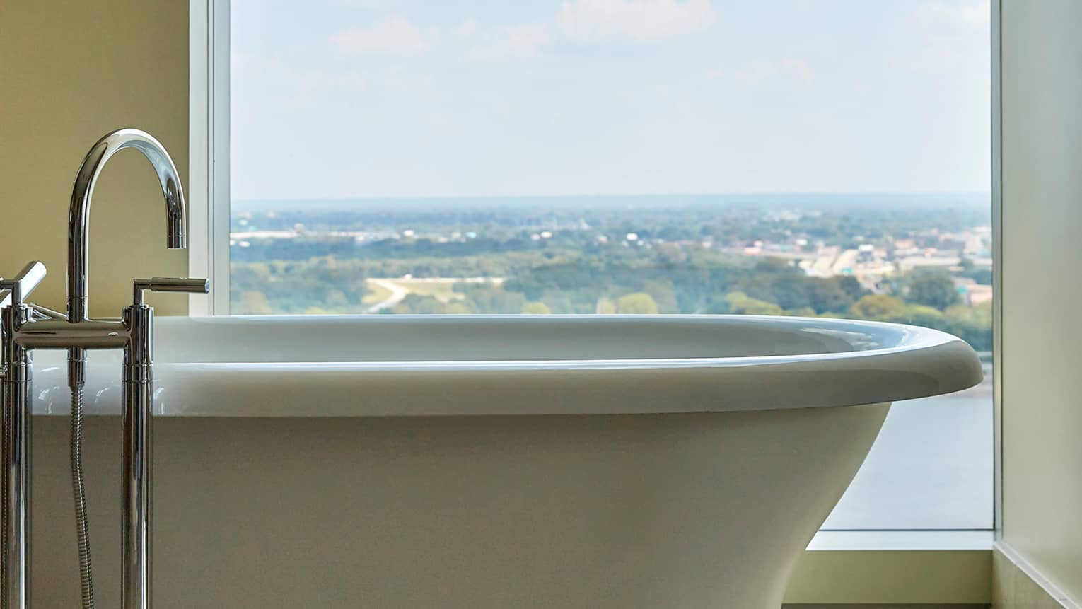 Close-up of large free-standing white tub against window overlooking river