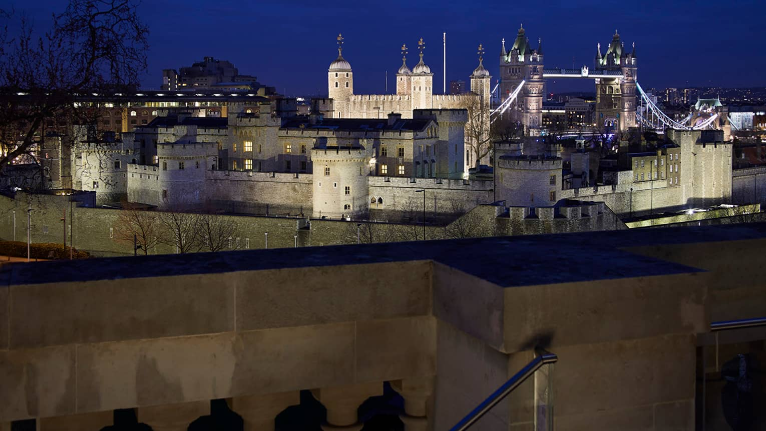 View over wall to Tower Bridge and the Tower of London at night