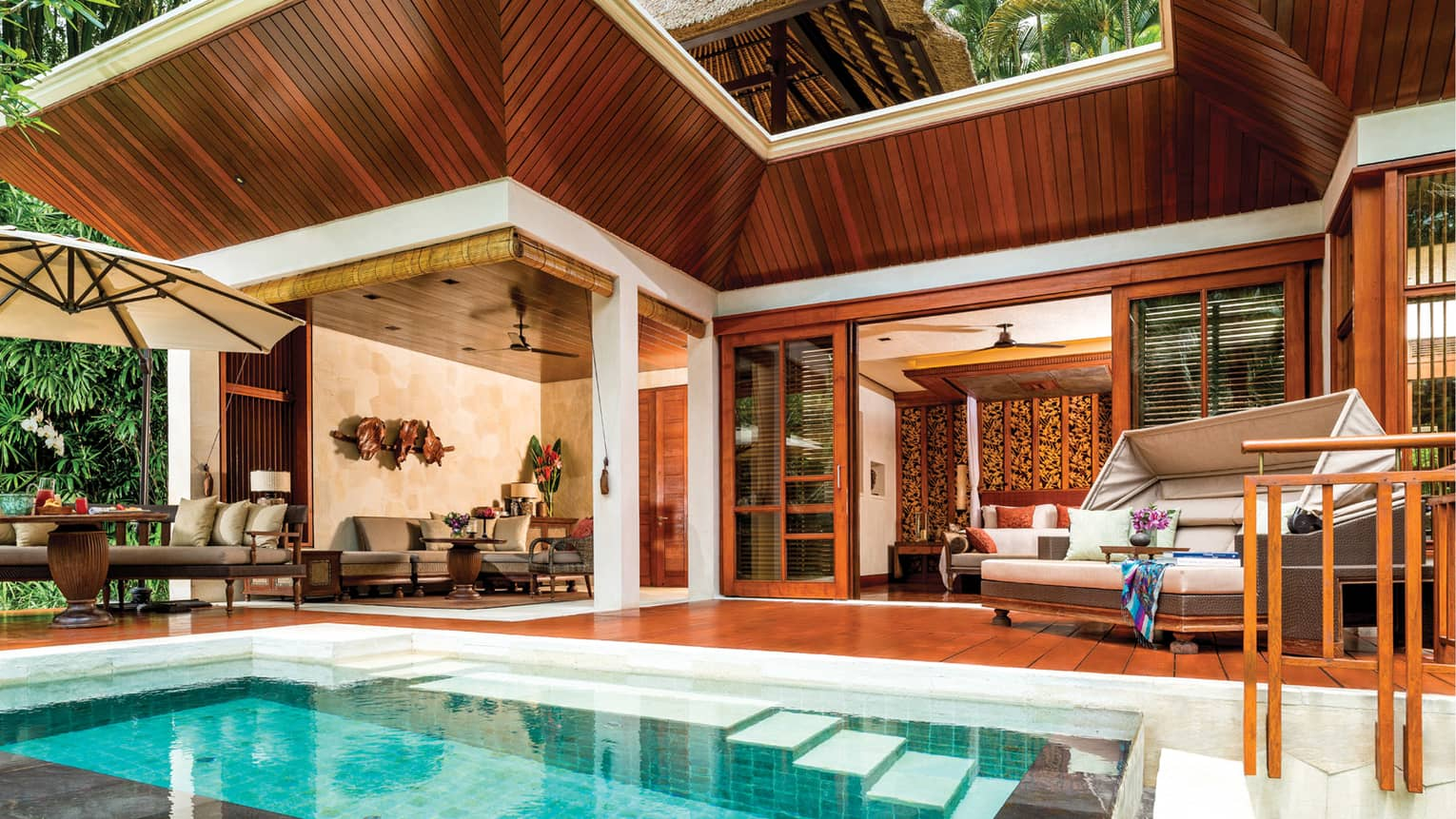 Small rectangular plunge pool in front of wood patio with beige sofas and dining chairs, wood villa roof