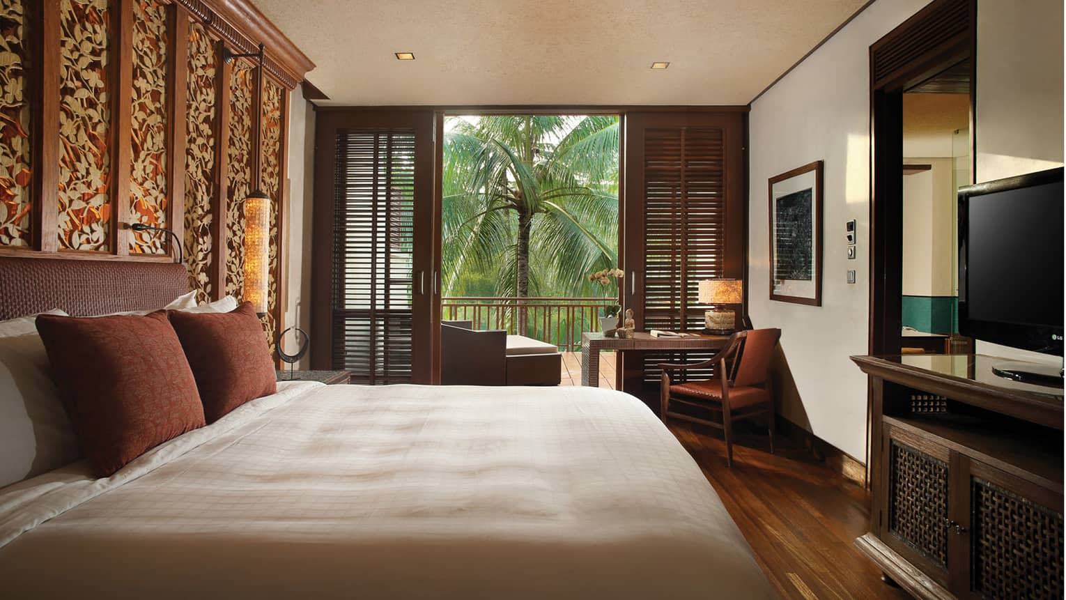 Family Suite bedroom with king-size bed, brown pillows, TV, wood shutters opening to patio with palm tree