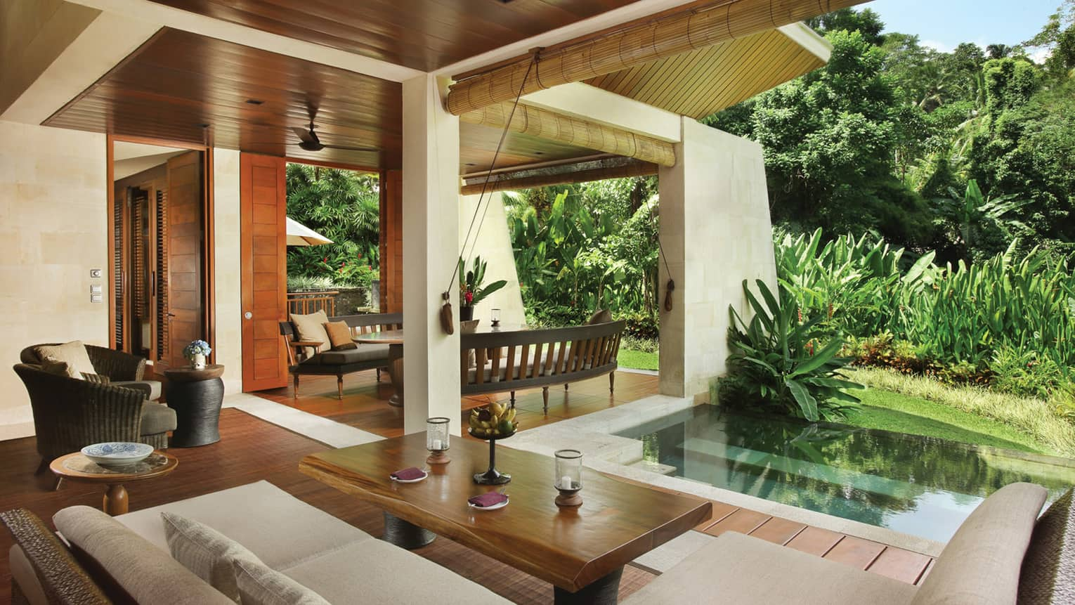 Two Bedroom Villa open-air living space with wood floors, white patio sofa, plunge pool beside green tropical plants