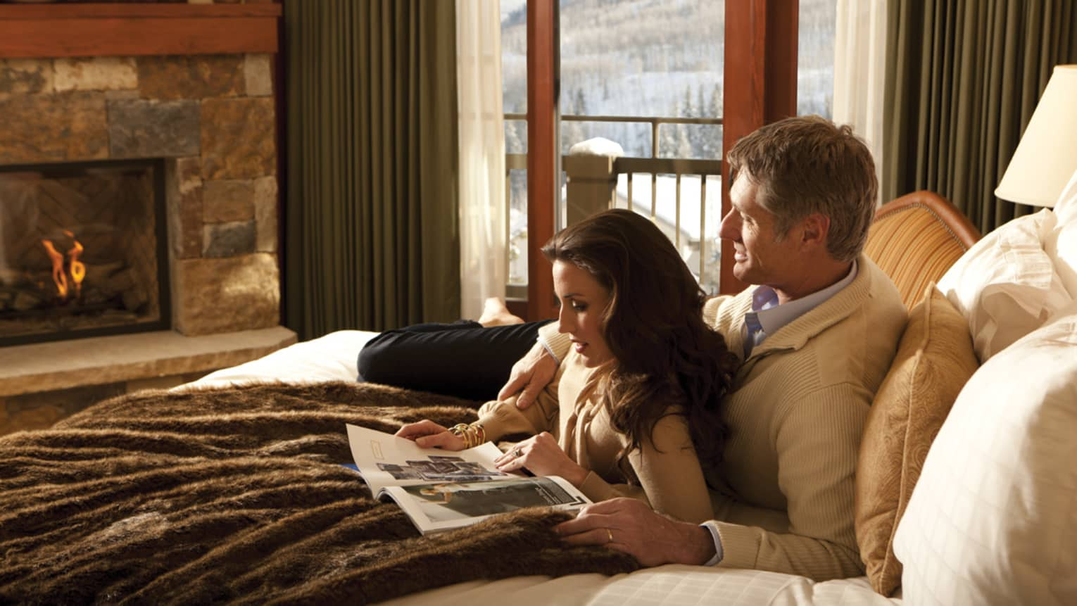 Man and woman read magazine and cuddle on bed with soft brown bedspread in front of stone fireplace