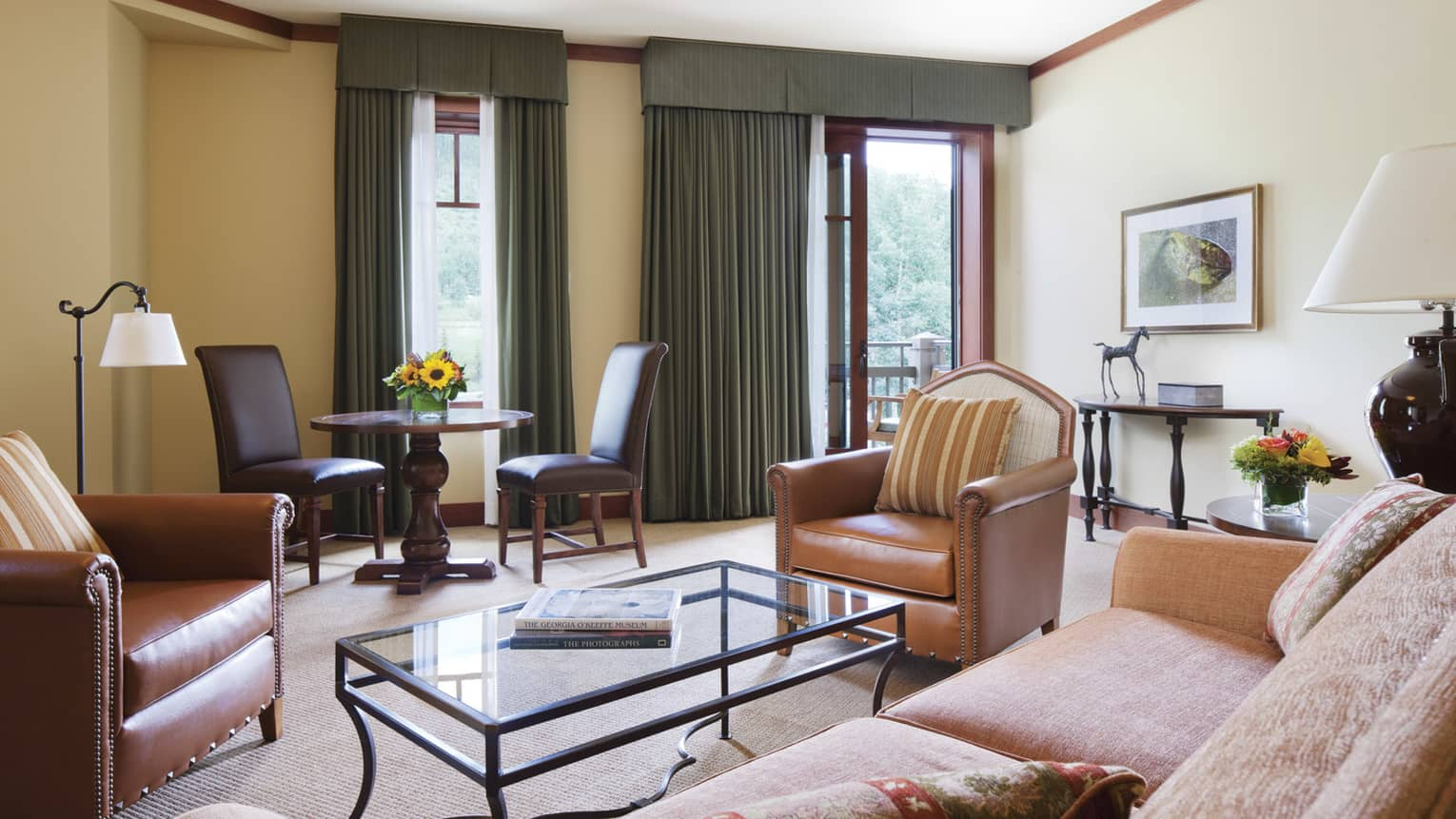 Mountain-View Executive Suite living room with sofa, glass coffee table with photo books, leather armchair