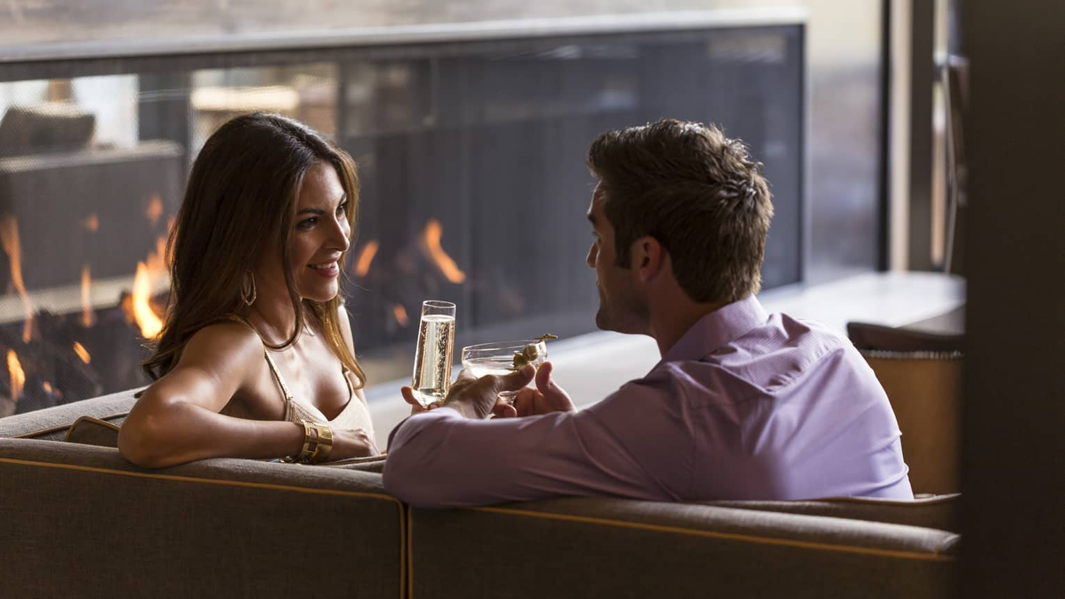 Woman with champagne and man with martini relax on sofa near modern fireplace