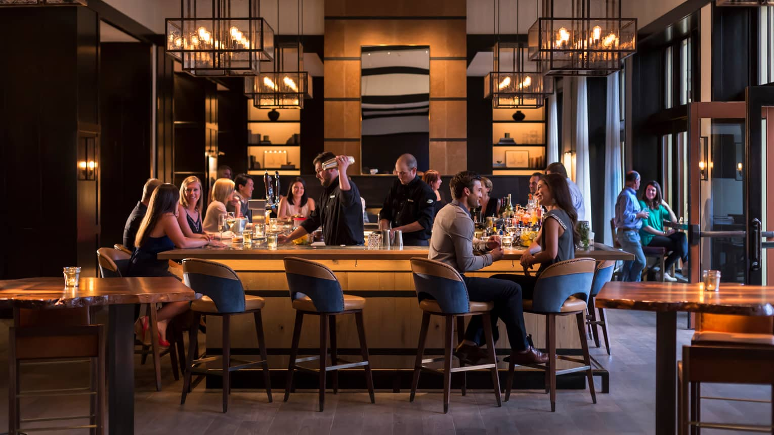 Guests socialize around wood bar with mid-century style stools and chandeliers as bartender makes martini