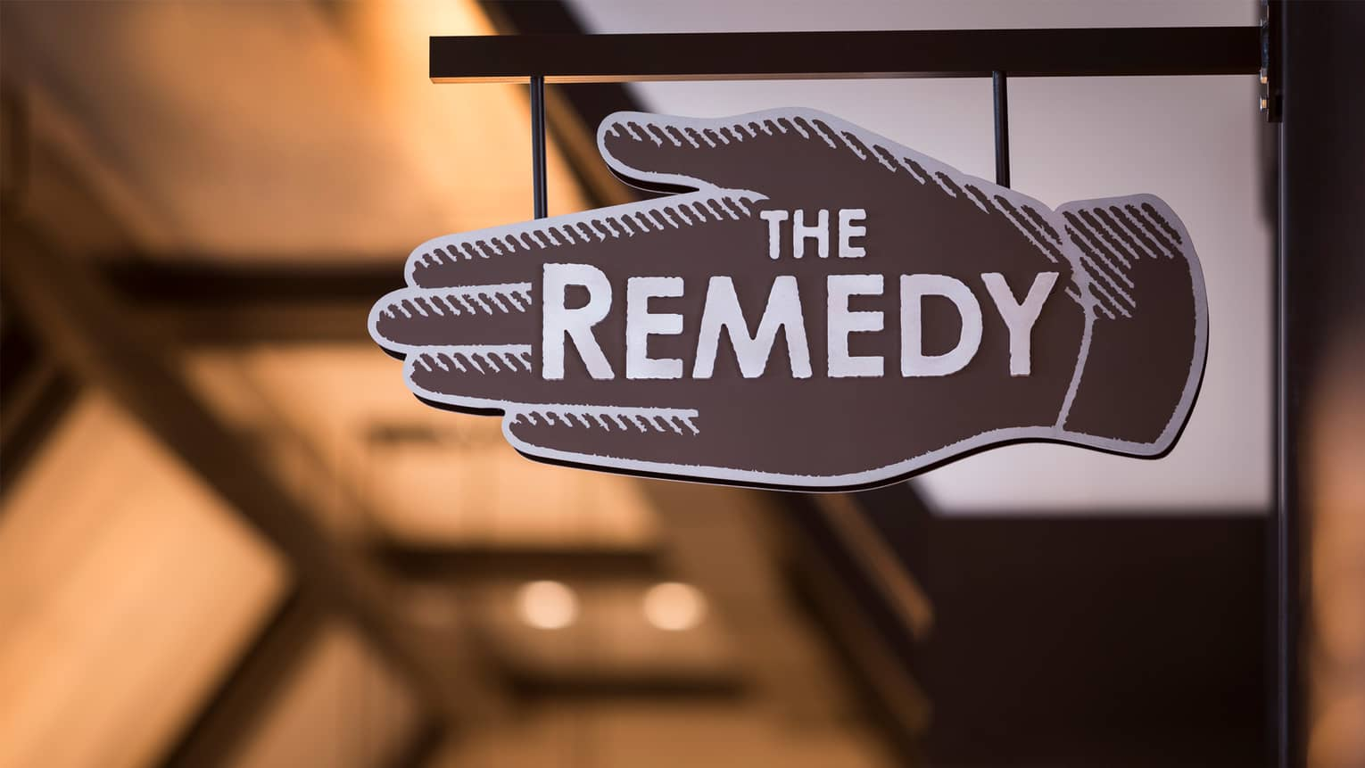 Close-up of The Remedy Bar brown-and-white hand-shaped sign