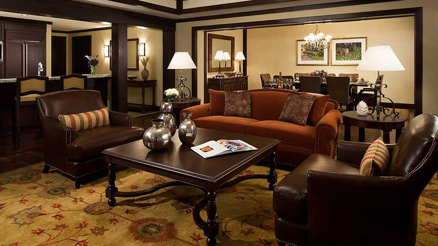 Two-bedroom with den residence suite living space with dark wood decor, private dining table, kitchenette