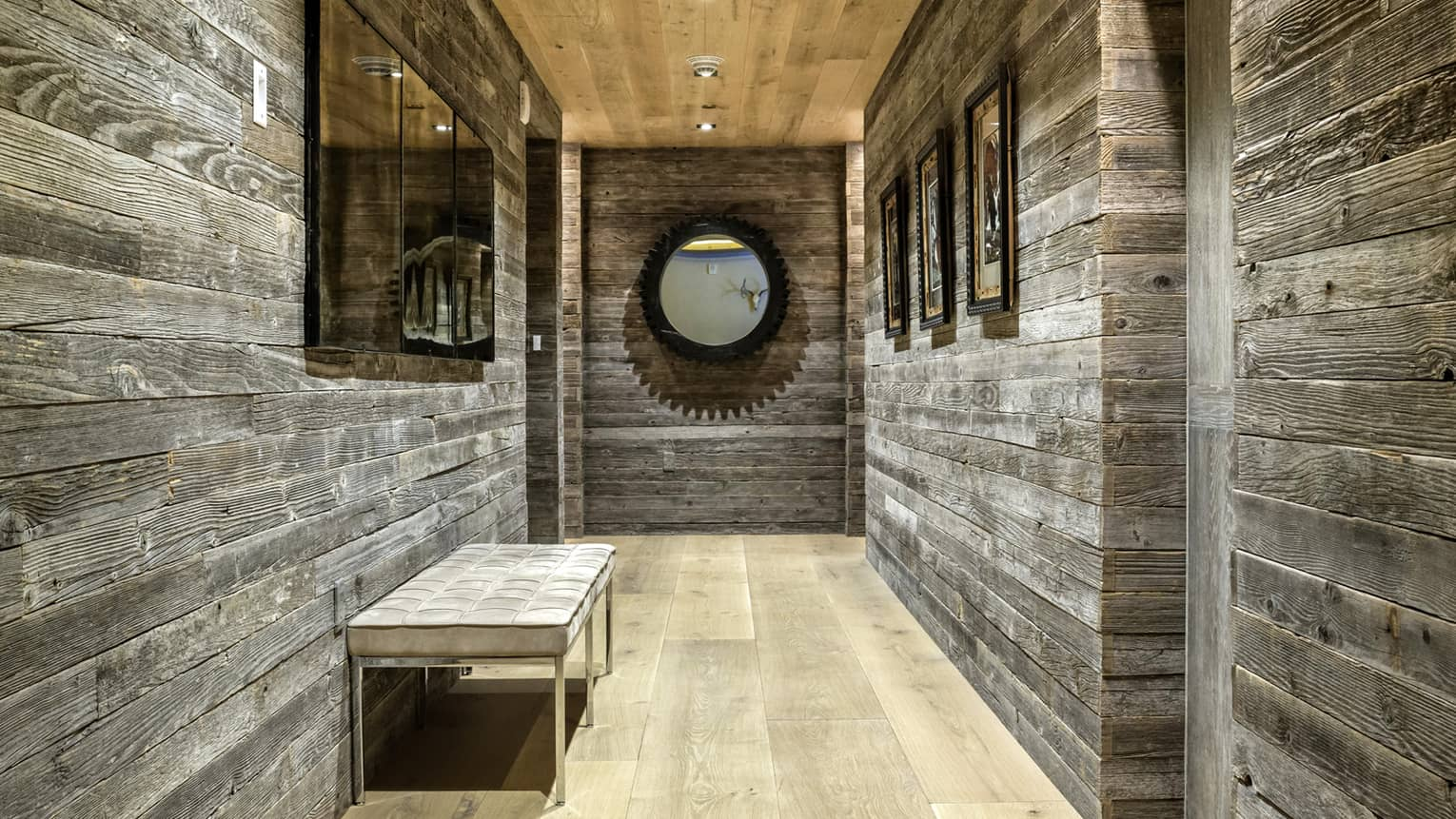 Hallway with barn wood walls, mirror, plush bench
