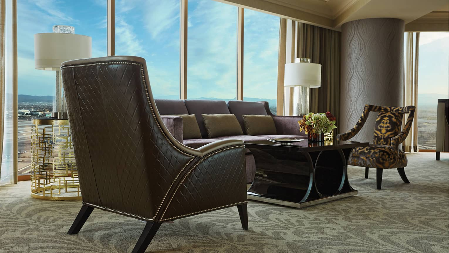 Hotel suite modern brown leather armchairs, sofa against sunny window