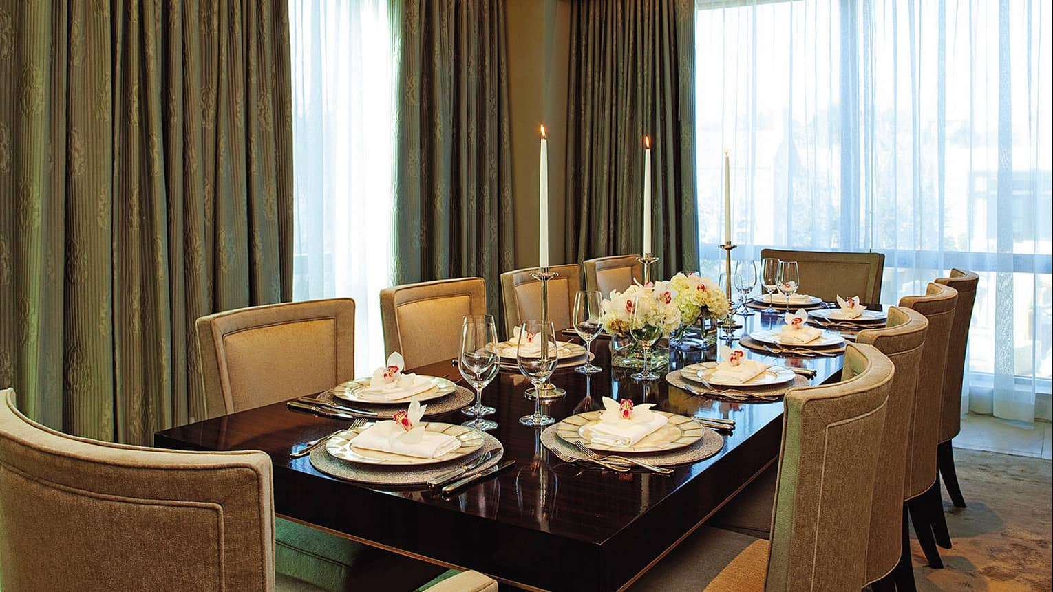 Royal Suite large private dining table elegantly set with fine dinnerware, tall single white candles, fresh flowers, in front of corner windows