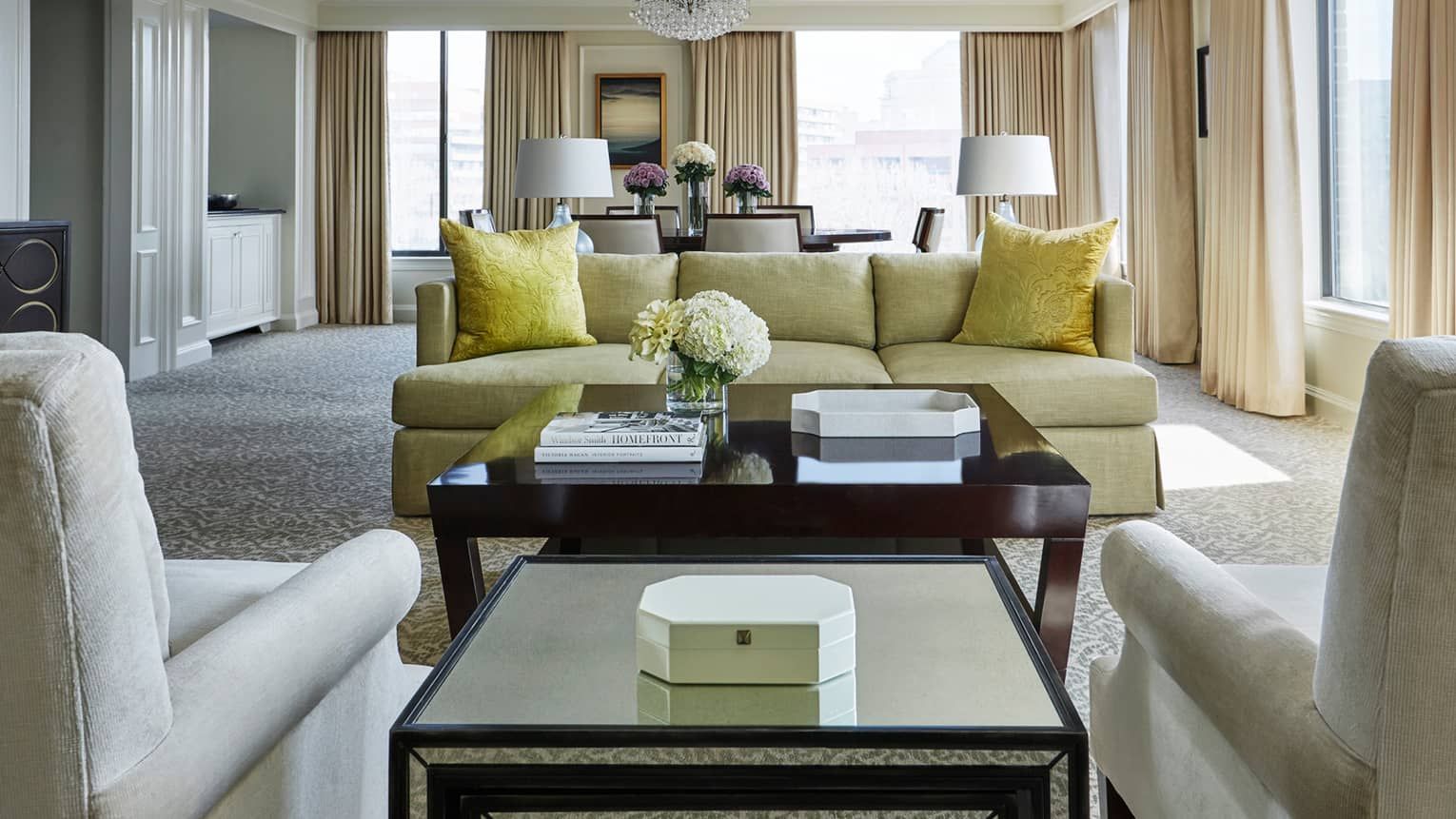 Presidential Suite East Wing living room with two white armchairs yellow sofa and accent pillows in front of dining room