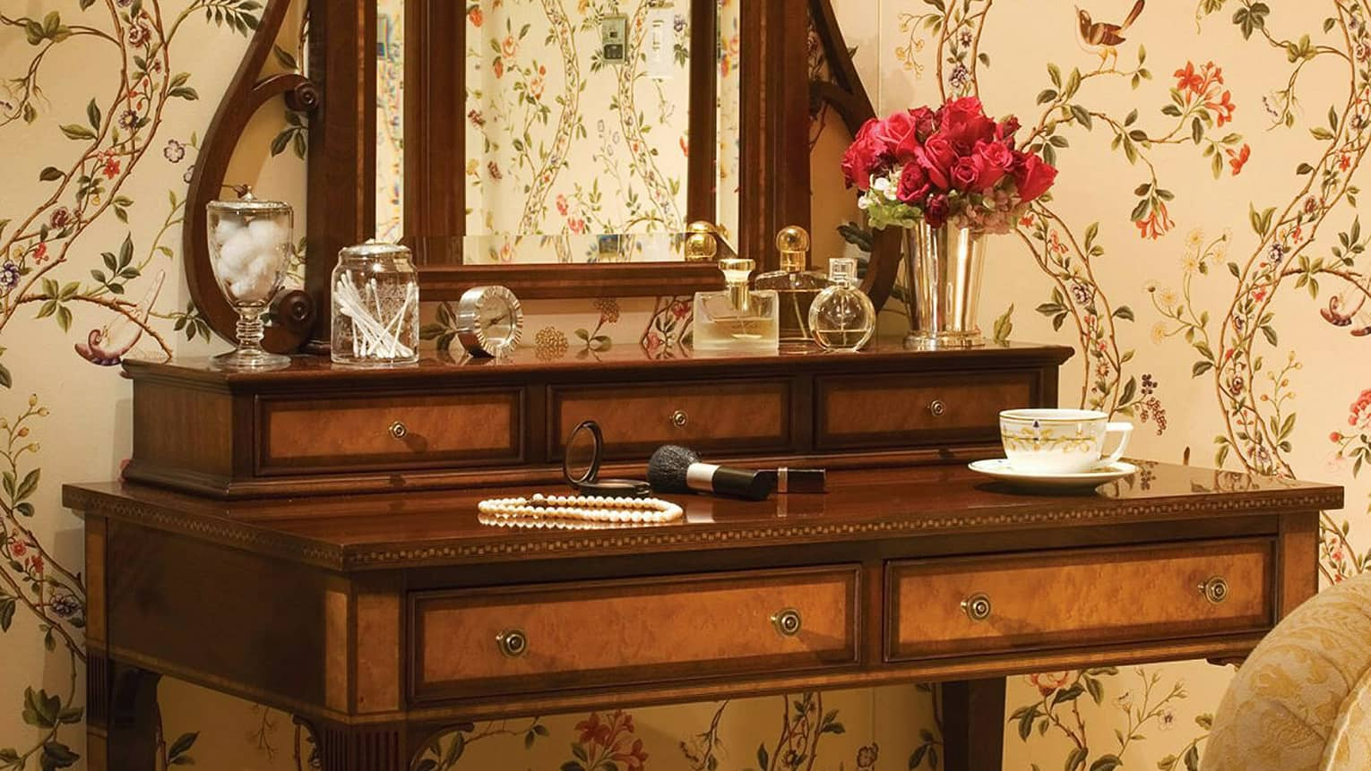 Antique-style wood vanity, mirror with perfume bottles, make-up, pearl necklace