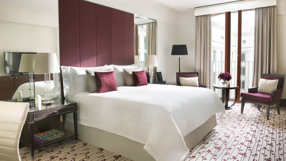 Deluxe Room bed with burgundy fabric headboard, accent pillows and chair, purple flowers in glass vase