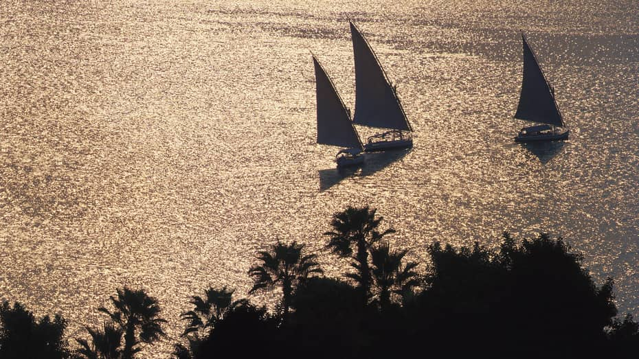 Silhouettes of three sailboats on Nile river at dusk
