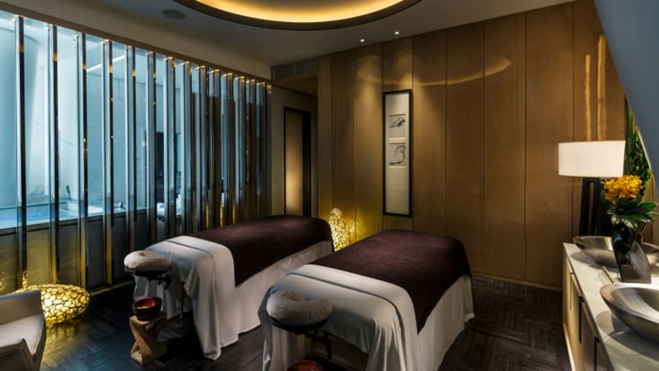 Two massage tables with burgundy blankets side-by-side in dark room with dim lights, lanterns, near tub